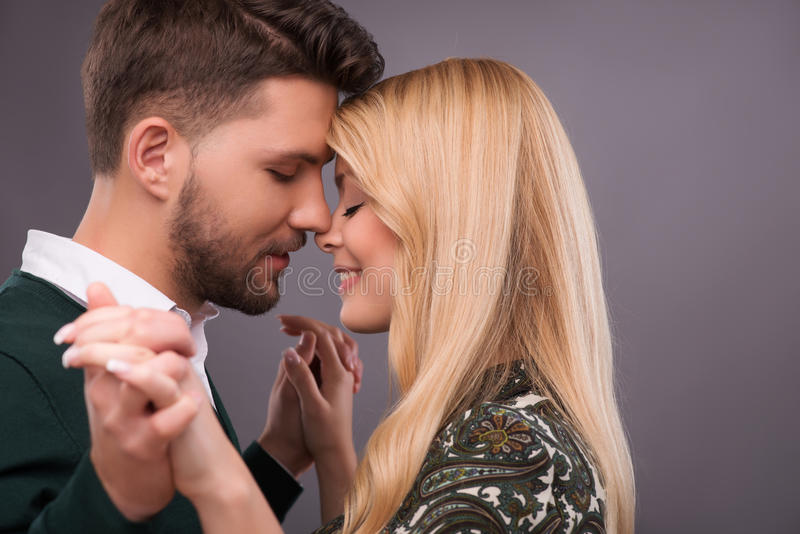 Lovely beautiful couple. Half-length portrait of lovely happy smiling couple standing with closed eyes facing each other dancing enjoying the moment they are stock photography
