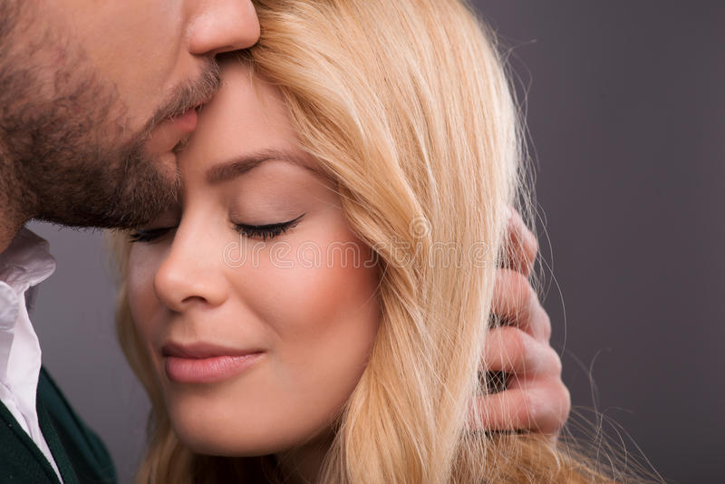 Lovely beautiful couple. Half-length portrait of lovely happy smiling couple standing with closed eyes facing each other enjoying the moment they are together stock image