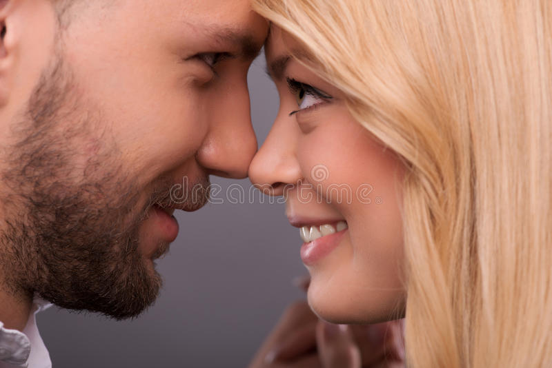 Lovely beautiful couple. Selective focus on the lovely happy couple standing with closed eyes facing each other enjoying the moment they are together royalty free stock images