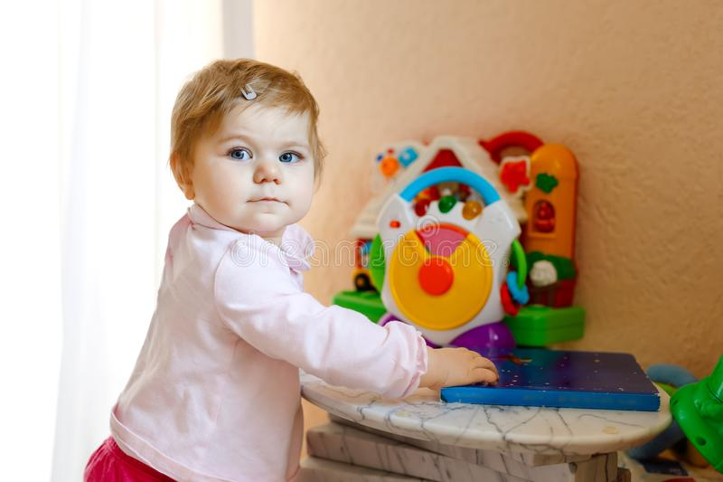 Lovely beautiful cute beautiful little baby girl playing with educational toys at home or nursery. Happy healthy child stock photo