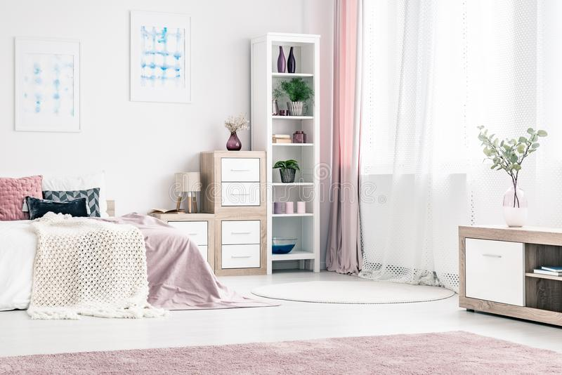 Lovely bedroom interior. Lovely, cozy bedroom interior design with king size bed, shelves, posters, rugs and curtains stock image