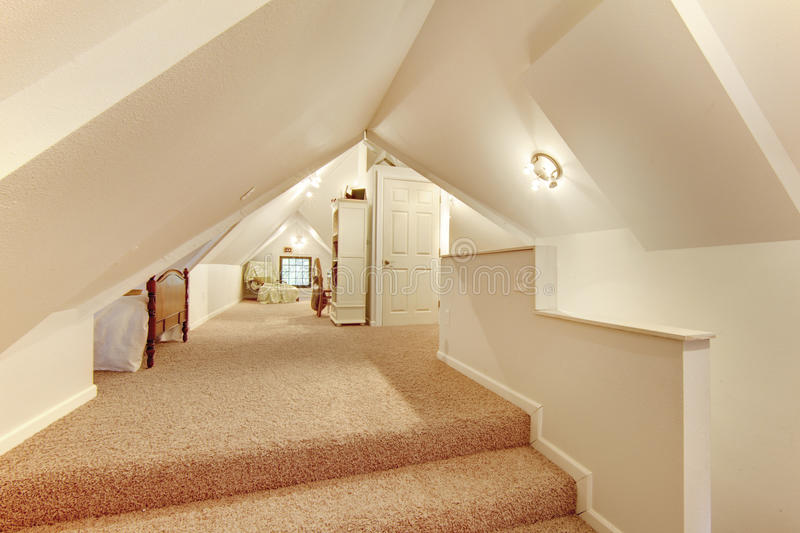 Lovely beige attic bedroom with vaulted ceiling and carpet floor royalty free stock photos