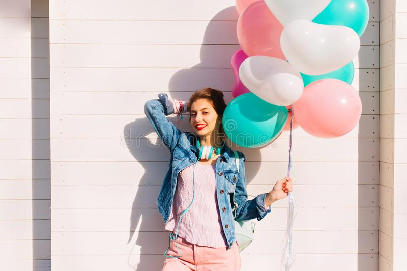 Lovely birthday girl in pink clothes and earphones received a bunch of colorful balloons as gift. Attractive young woman stock photography