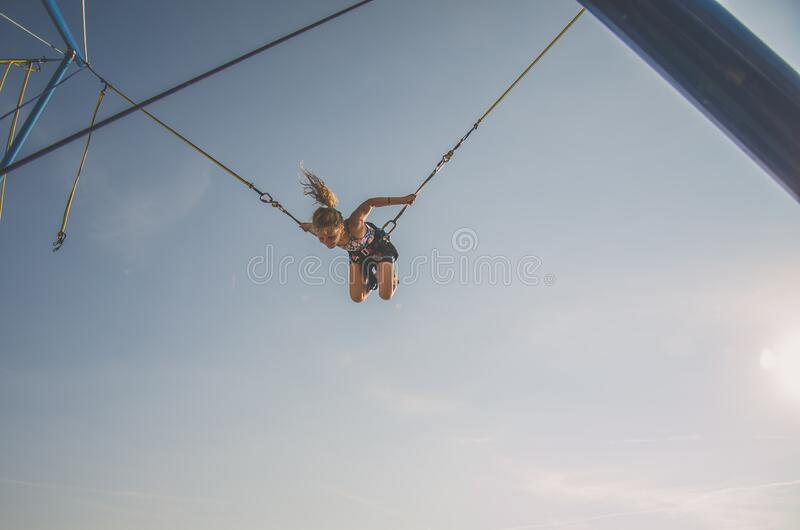 Lovely blond caucasian girl jumping and spinning around in the jump attraction in the playground. Little kid having fun in the bungee jumping attraction flying royalty free stock images