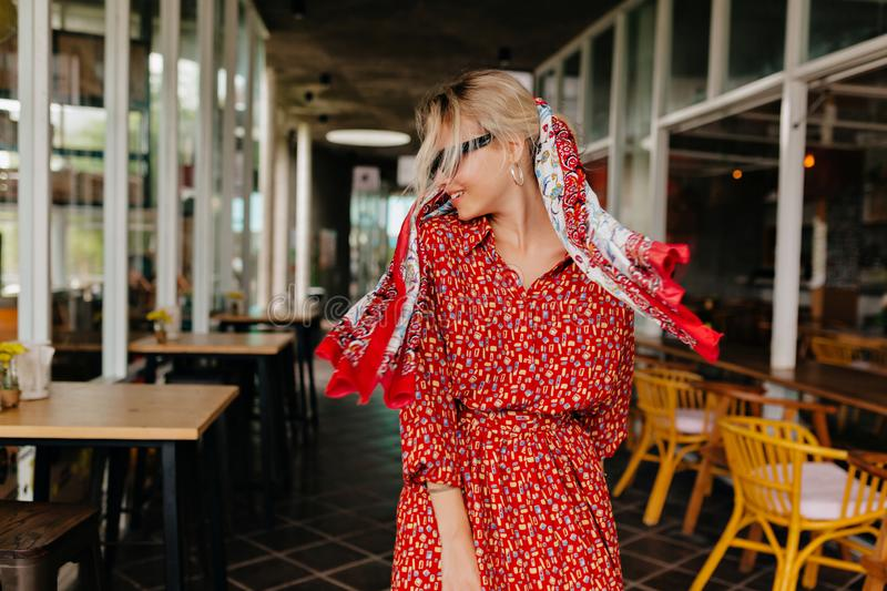 Lovely blond happy woman walking outside wearing bright red dress and shawl in the head, has fun and dancing royalty free stock photos