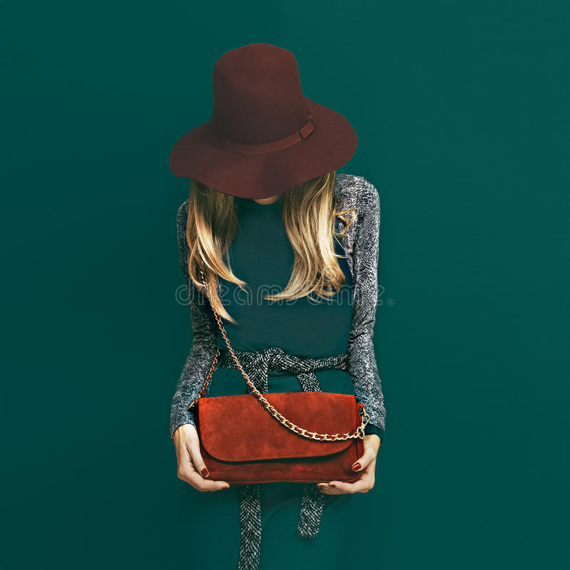 Lovely blond model in fashionable red hat and a red clutch on gr stock photos
