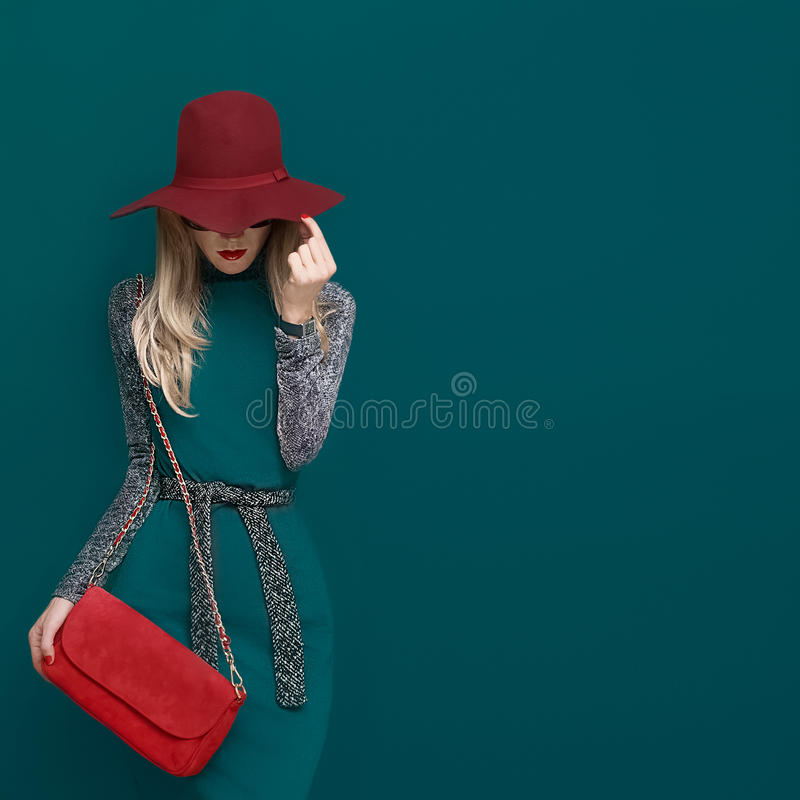 Lovely blond model in fashionable red hat and a red clutch on gr. Een background royalty free stock image