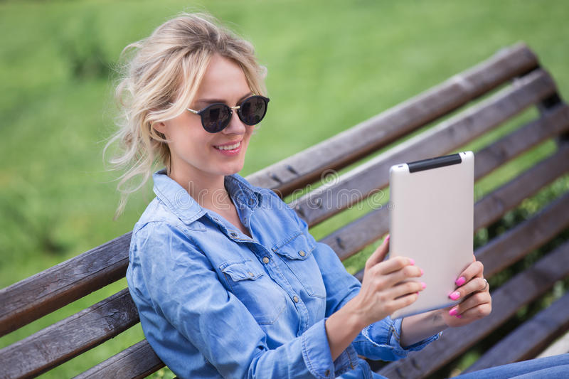 Lovely blond woman with electronic tablet in hands stock photos