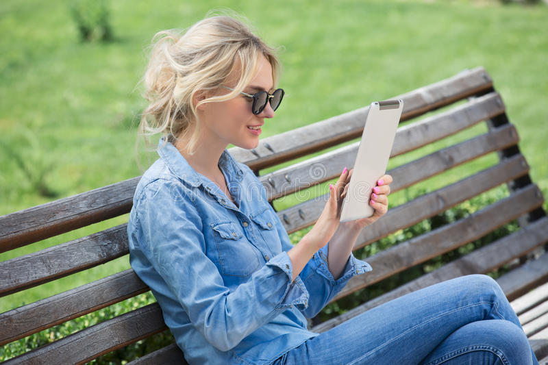 Lovely blond woman with electronic tablet in hands stock images