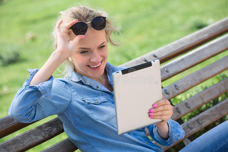 Lovely blond woman with electronic tablet in hands stock image