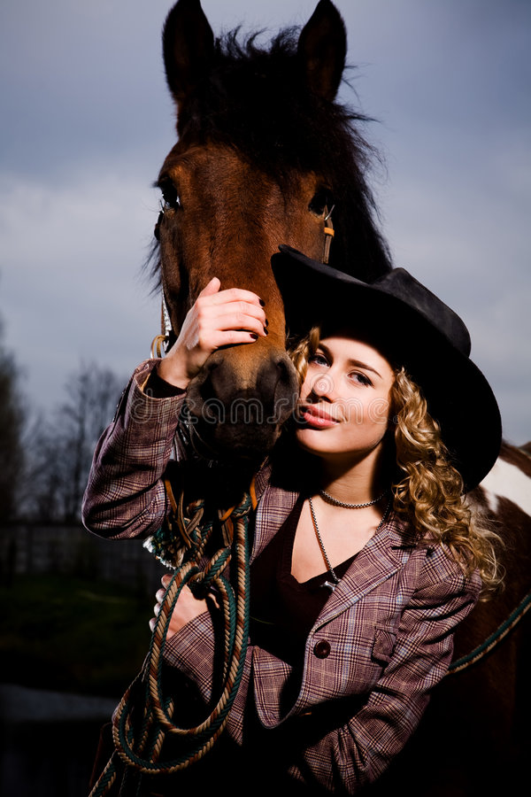 Lovely blond woman in a hat standing by horse royalty free stock photo
