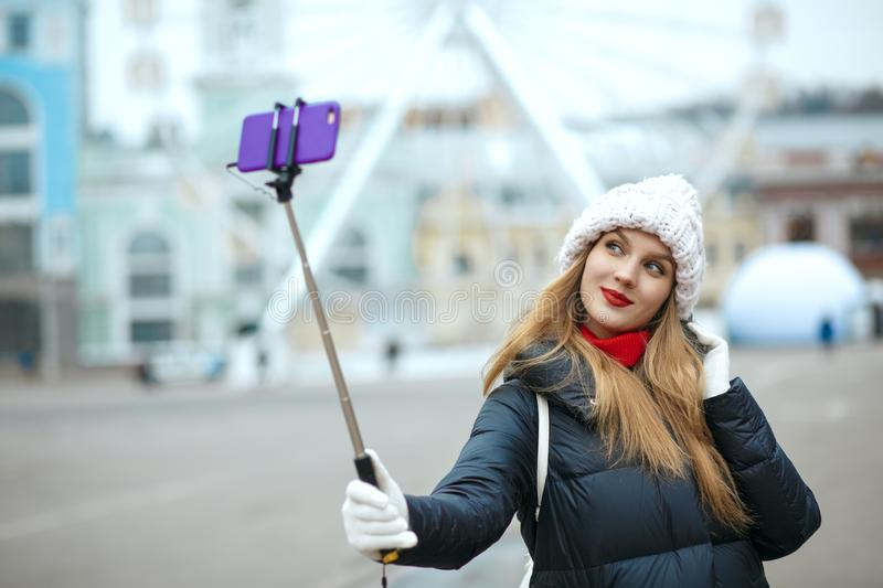 Lovely blonde girl tourist wearing knitted cap, taking selfie at stock images