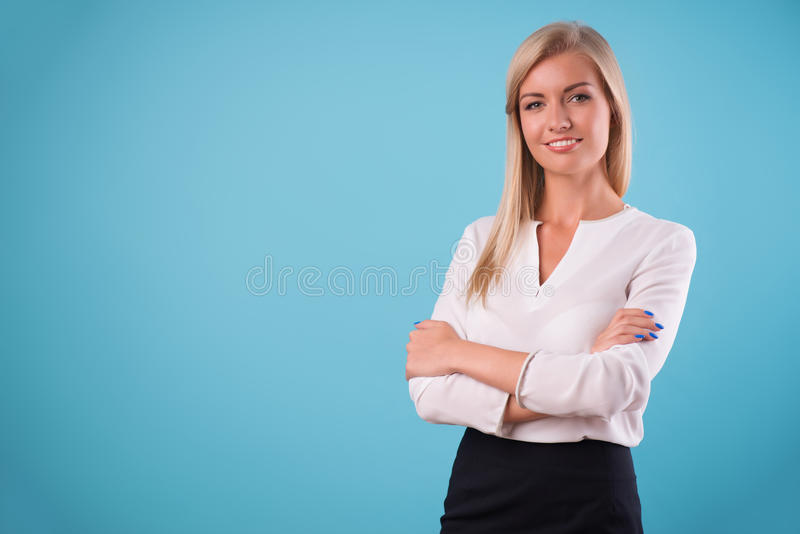 Lovely blonde wearing white blouse. Half-length portrait of beautiful smiling blonde wearing white classic blouse standing aside cross-armed looking at us royalty free stock images