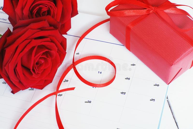 Lovely blooming red color rose flower and elegant gift box on 14 Fab calender background decorated with red ribbon, sweet. Valentine present concept, copy space stock images
