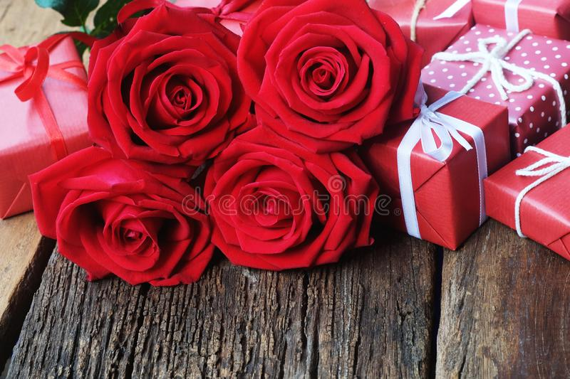 Lovely blooming red color rose flower and elegant gift box on wood table background decorated with mini red heart figure, sweet. Valentine present concept, copy royalty free stock photo