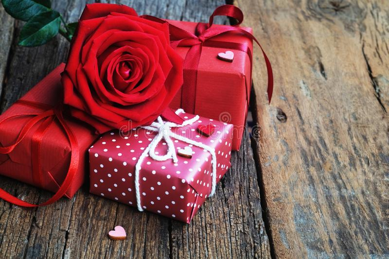 Lovely blooming red color rose flower and elegant gift box on wood table background decorated with mini red heart figure, sweet. Valentine present concept, copy royalty free stock image
