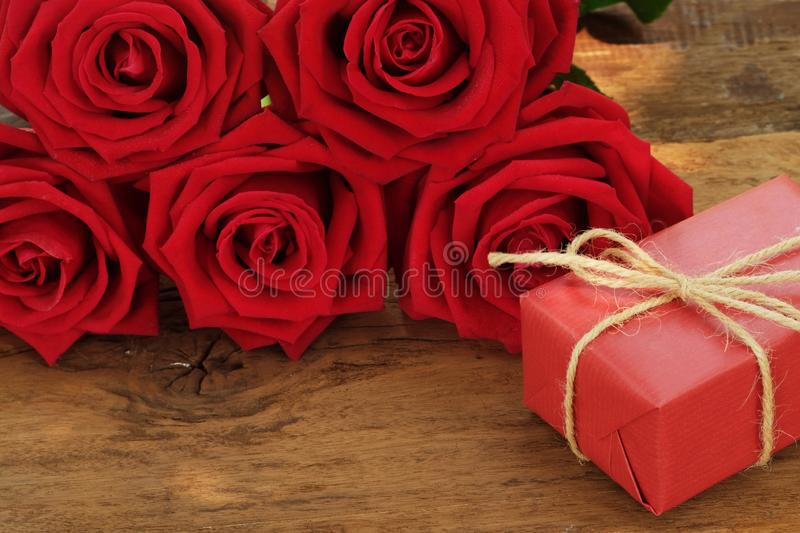 Lovely blooming red color rose flower and elegant gift box on wood table background decorated with mini red heart figure, sweet. Valentine present concept, copy stock images