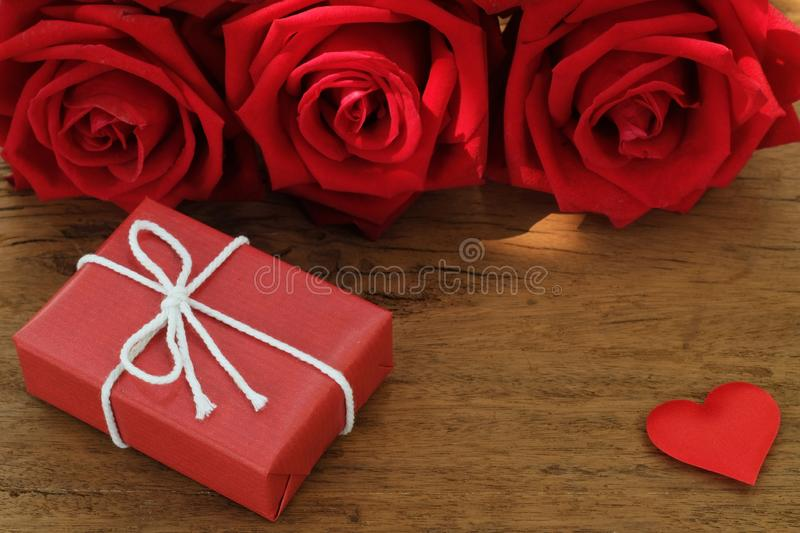 Lovely blooming red color rose flower and elegant gift box on wood table background decorated with mini red heart figure, sweet. Valentine present concept, copy royalty free stock images