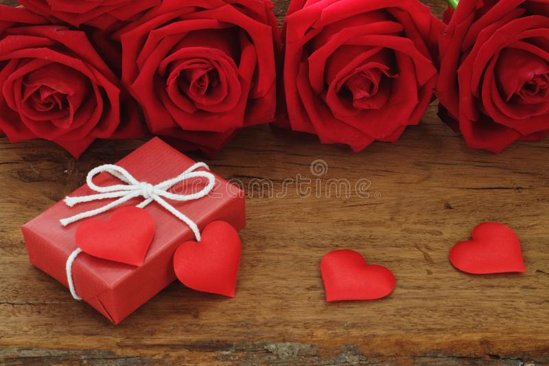 Lovely blooming red color rose flower and elegant gift box on wood table background decorated with mini red heart figure, sweet. Valentine present concept, copy stock image