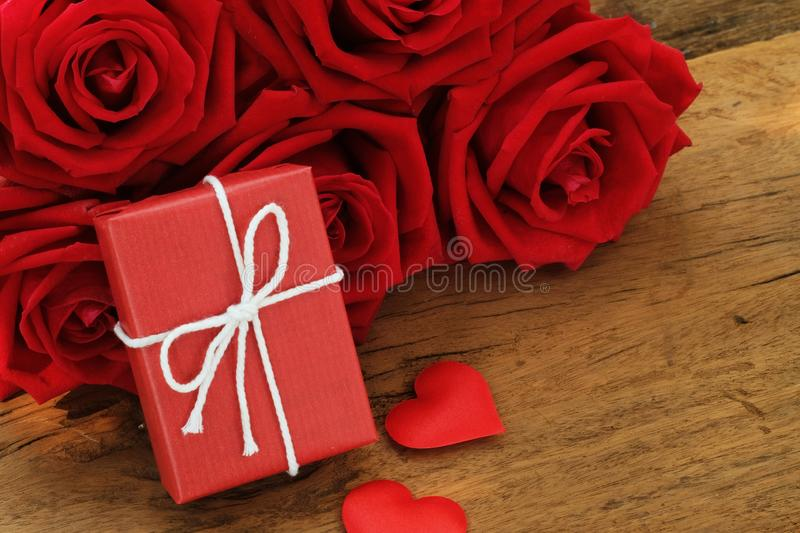 Lovely blooming red color rose flower and elegant gift box on wood table background decorated with mini red heart figure, sweet. Valentine present concept, copy stock photos