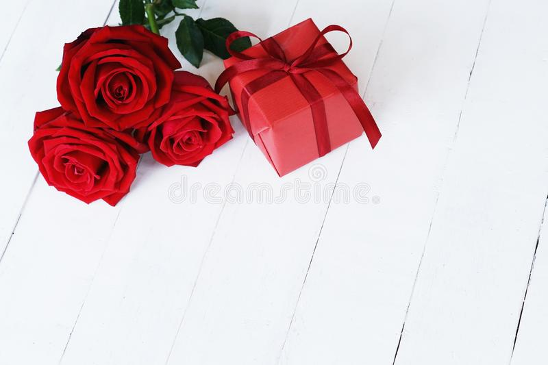 Lovely blooming red color rose flower and elegant gift box on wood table background decorated with mini red heart figure, sweet. Valentine present concept, copy stock photography