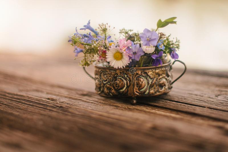 Lovely bouquet of meadow flowers in a small vase on a rustic wooden background. stock image