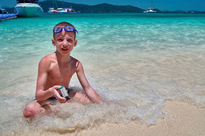 Lovely boy with swimming goggles sits in the turquoise water of the tropical sea surf line. royalty free stock photos