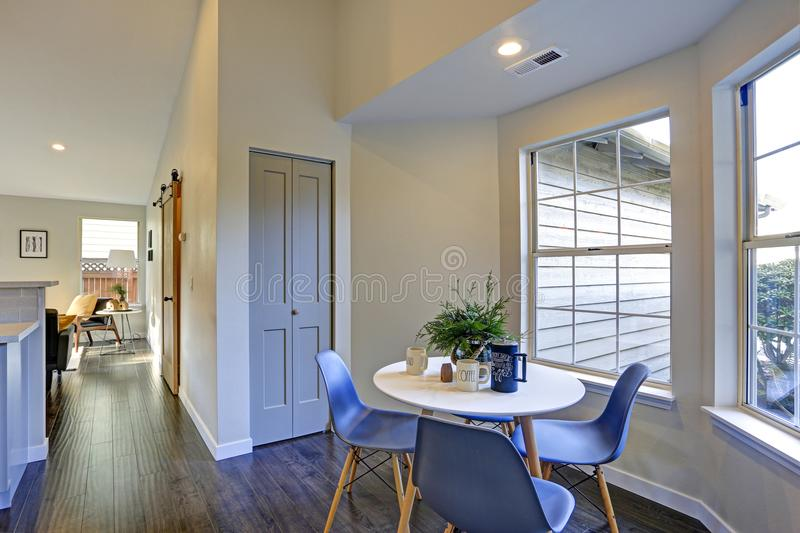 Lovely breakfast nook with white round table and blue chairs. Lovely breakfast nook fitted with white round table and blue chairs stock photography