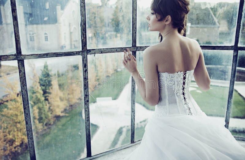 Lovely bride waiting for her husband. Lovely brunette bride waiting for her husband royalty free stock image
