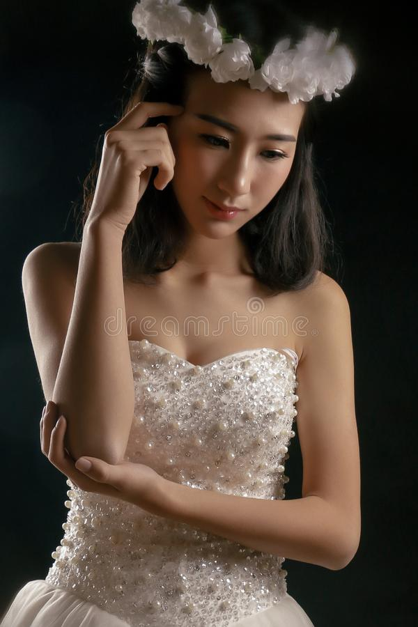 The lovely bride in the wedding dress. Isolated on black background.Her smile was sweet stock photos