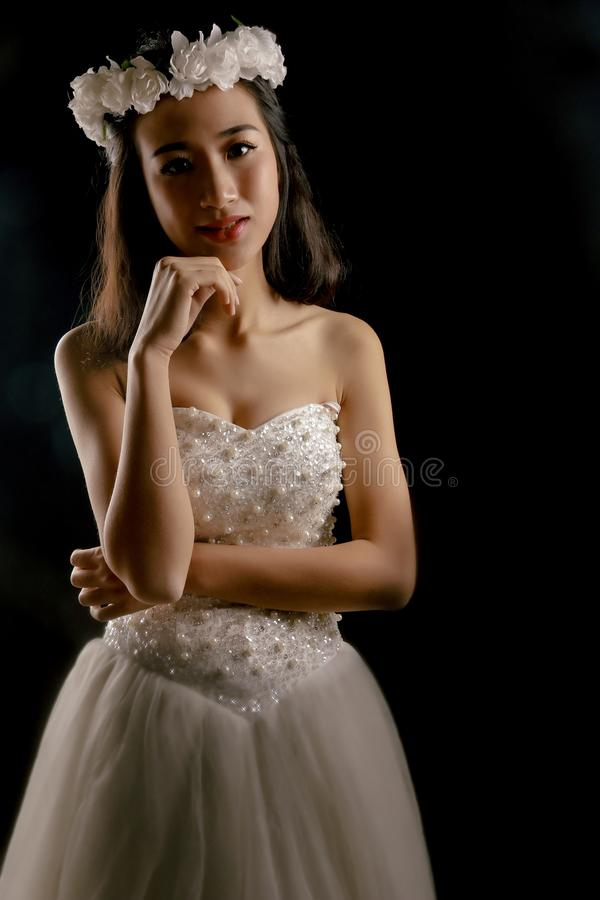 The lovely bride in the wedding dress. Isolated on black background.Her smile was sweet stock photography