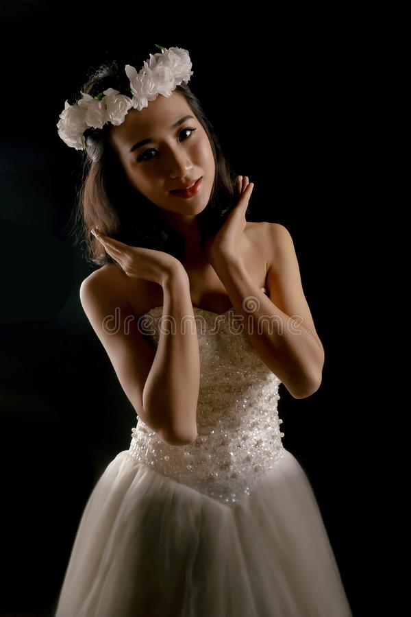 The lovely bride in the wedding dress. Isolated on black background.Her smile was sweet royalty free stock photo