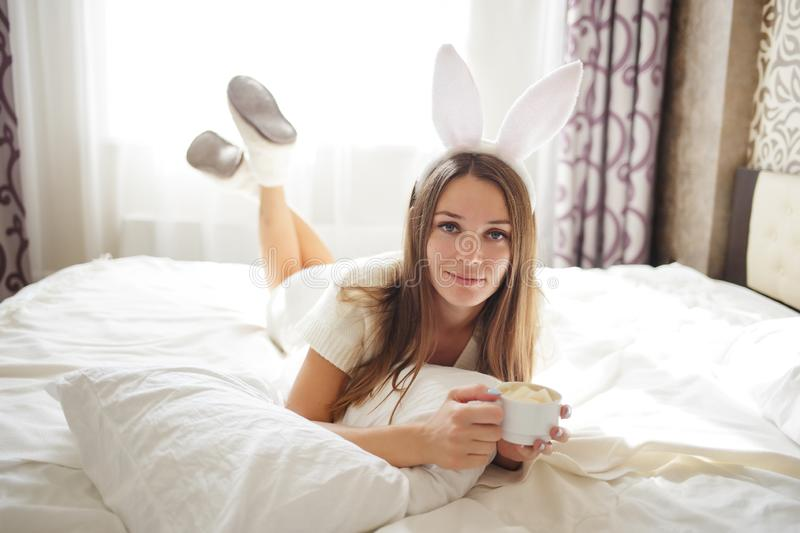 Lovely brunette girl with bunny ears on her head and lying with coffee on a bed in her bedroom stock photo