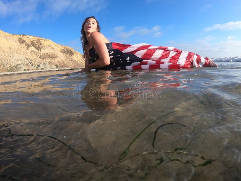 A Lovely Brunette Model Poses Nude At The Coast With An American Flag. A gorgeous brunette model poses nude with an American Flag At The Beach stock image