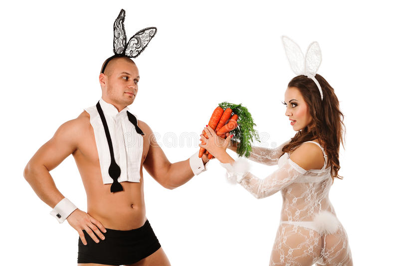 Lovely bunny couple. Lovely couple in rabbit costumes with carrots royalty free stock image