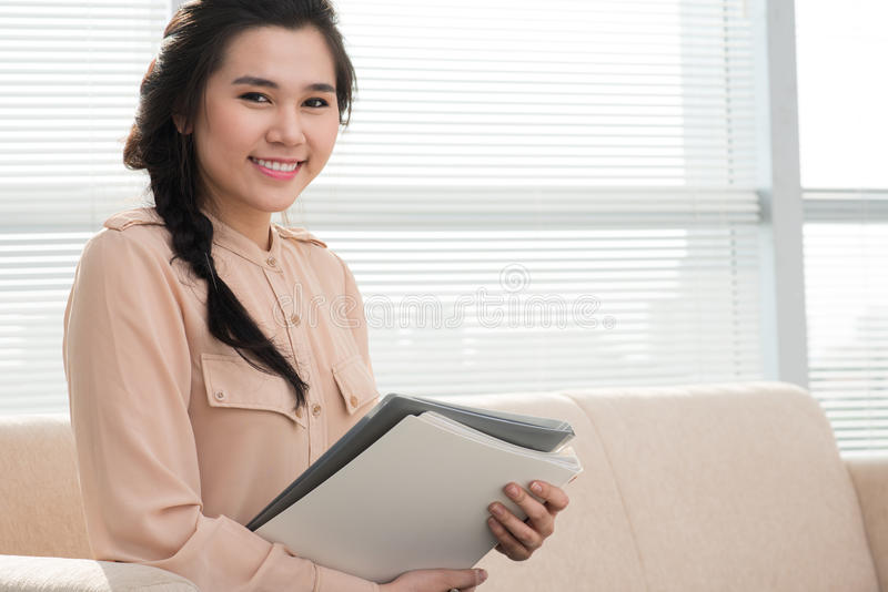 Lovely businesswoman. Portrait of a young businesswoman with a folder in hands royalty free stock photography