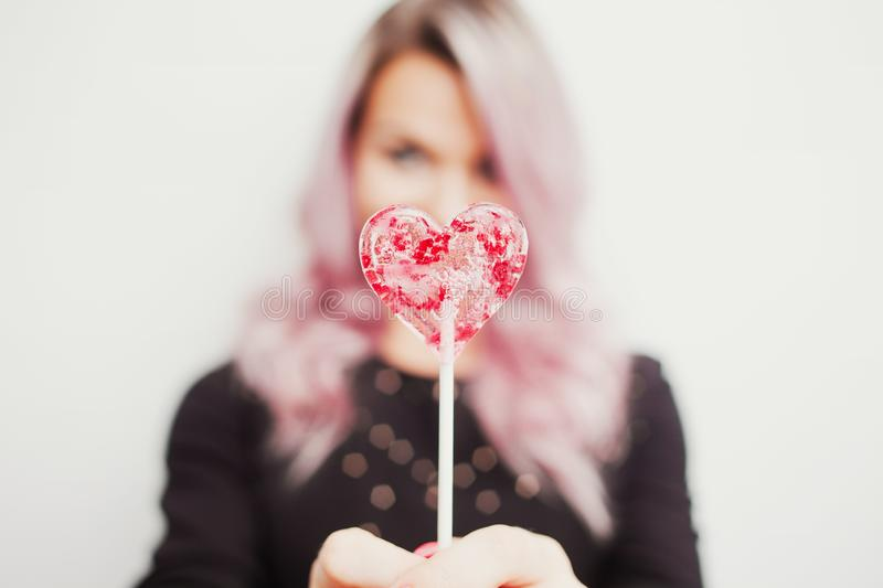 Lovely charming girl with a Lollipop in the form of heart. Portrait of a young woman with pink hair and pink candy royalty free stock photography