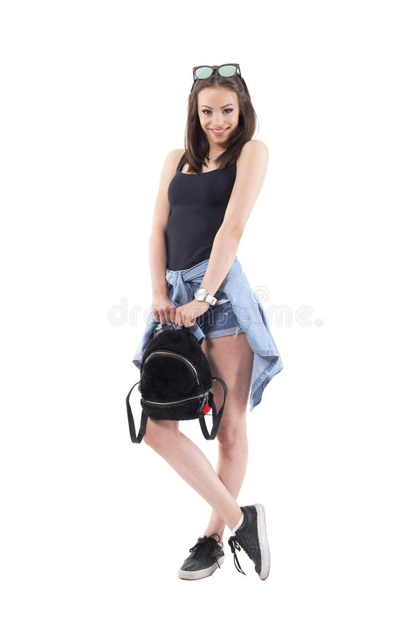 Lovely charming pretty girl with stylish fluffy bag and jeans shirt tied around hips smiling royalty free stock images