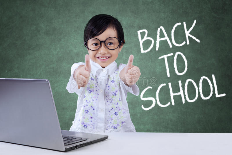 Lovely child back to school and show OK sign. Portrait of female elementary school student back to school and showing OK sign with a laptop on the table stock images