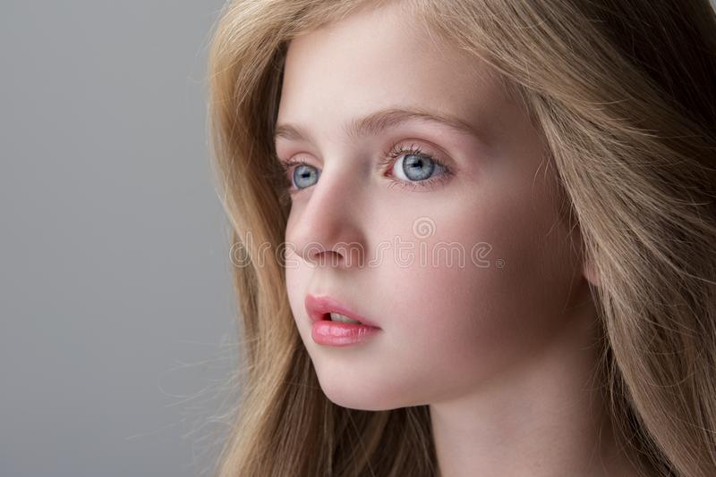 Lovely child is posing with pensiveness. Feeling sadness. Close-up of face of adorable serious little girl is standing and looking aside thoughtfully. Focus on stock photos