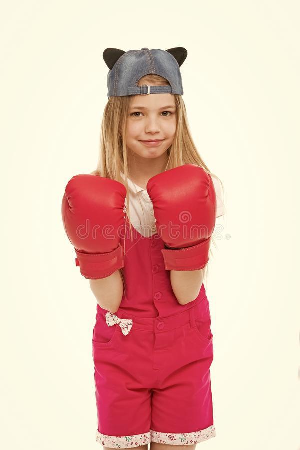 Lovely child wearing huge red boxing gloves. Girl in pink overalls isolated on white background. Kid wearing cute cap. With animal ears backwards. Little stock photo