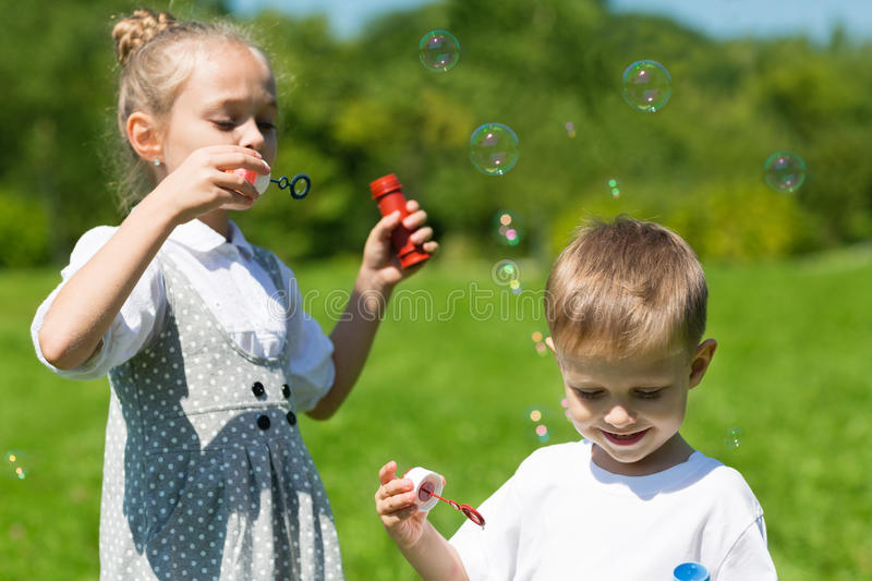 Lovely children blow soap bubbles. On a bright sunny day. Brother and sister stock photography