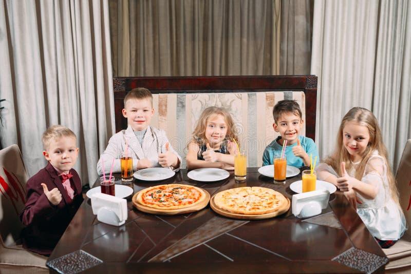 Lovely children eat pizza in the restaurant royalty free stock image