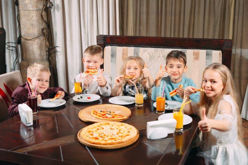 Lovely children eat pizza in the restaurant royalty free stock photo