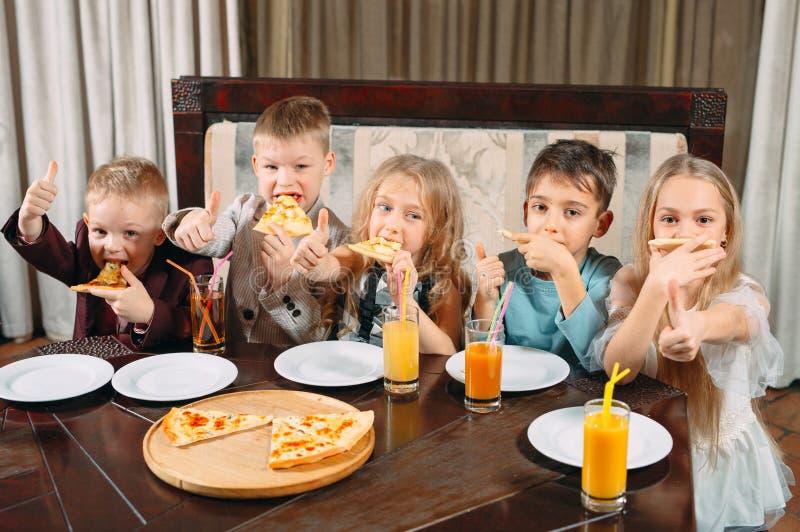 Lovely children eat pizza in the restaurant stock photos