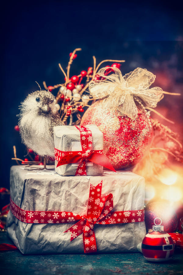 Lovely Christmas card with beautifully packed gifts, holiday balls , bird and festive bokeh lighting. royalty free stock image