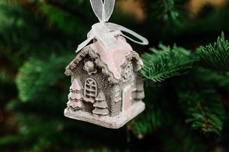 Lovely Christmas tree toy in the form of cute little house. Lovely Christmas tree decoration toy in the form of cute little house in snow on the green background stock images