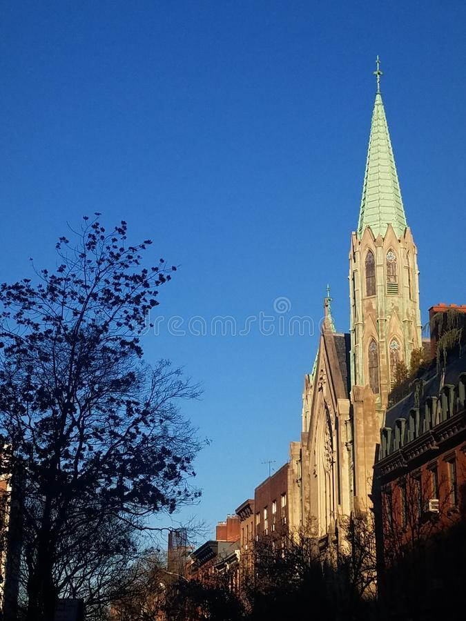 Lovely church with copper spire detail and Gothic architecture in historic neighborhood street. Located in the historic Chelsea district of New York City stock photography