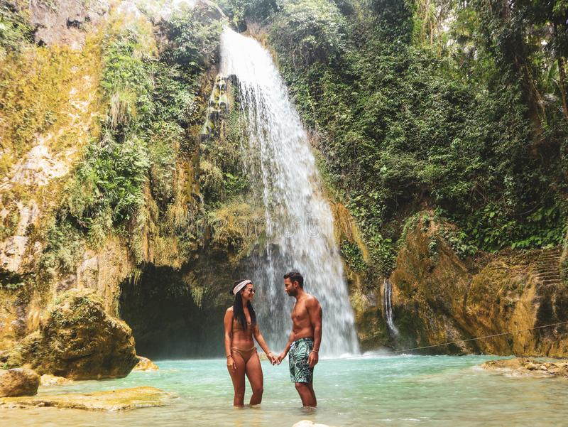 Lovely couple alone in deep forest waterfall, inambakan falls in Cebu Island in Philppines. Lovely couple alone in deep forest waterfall from mountain gorge at stock photo