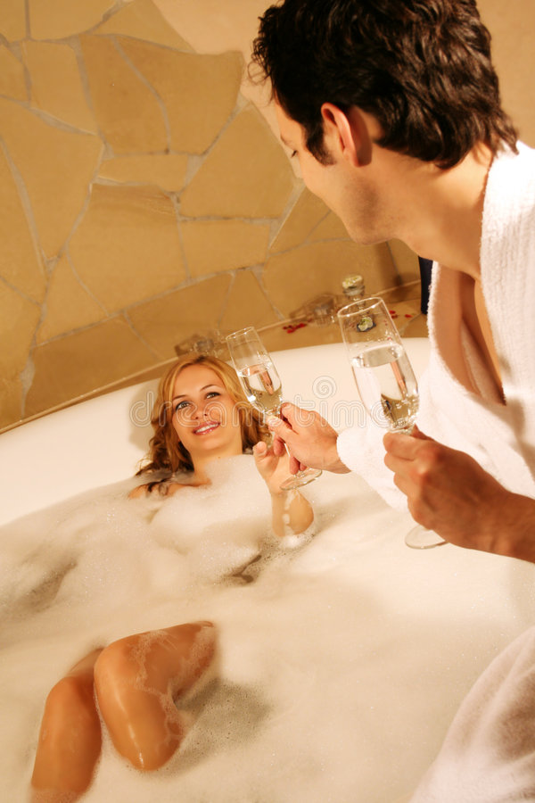 Lovely couple in bath. A young beautiful couple is taking a bath with champagne in a glass royalty free stock image